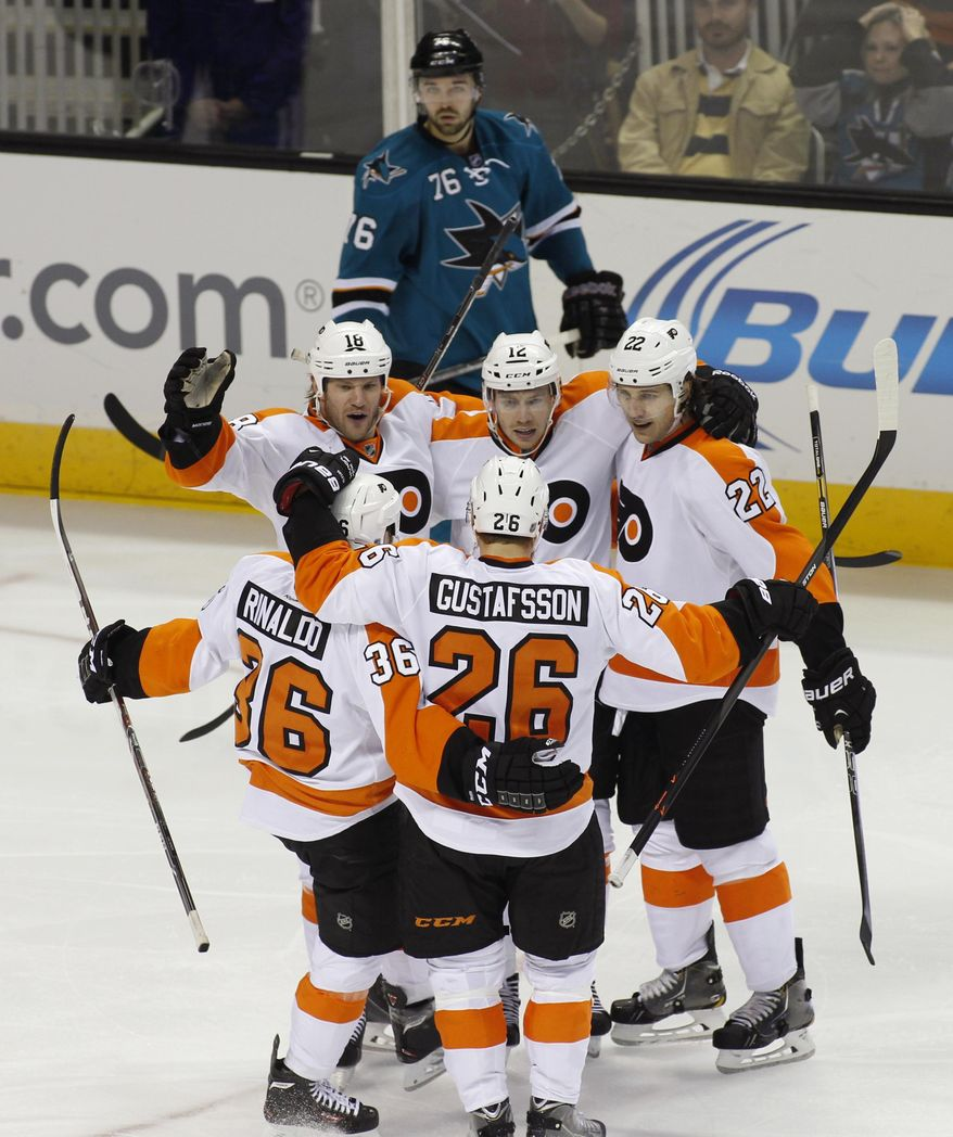 Philadelphia Flyers' Michael Raffi, center of group facing camera, celebrates with teammates, Adam Hall, left facing camera, Luke Schenn (22), Zac Rinaldo (36) and Erik Gustafsson (26) after scoring a goal against the San Jose Sharks during the third period of an NHL hockey game, Monday, Feb. 3, 2014, in San Jose, Calif. Sharks' Eriah Hayes is in the background. (AP Photo/George Nikitin)