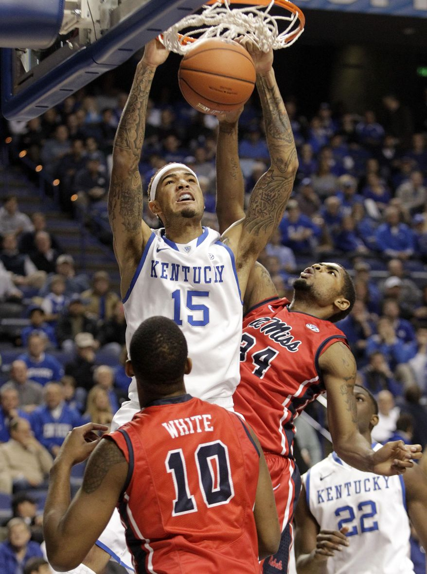 CORRECTS DAY TO TUESDAY Kentucky's Willie Cauley-Stein (15) dunks between Ole Miss' LaDarius White (10) and Aaron Jones during the first half of an NCAA college basketball game, Tuesday, Feb. 4, 2014, in Lexington, Ky. (AP Photo/James Crisp)