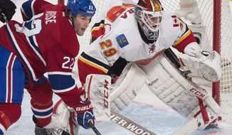 Montreal Canadiens' Dale Weise, left, moves in on Calgary Flames goaltender Reto Berra during the second period of an NHL hockey game Tuesday, Feb. 4, 2014, in Montreal. (AP Photo/The Canadian Press, Graham Hughes)