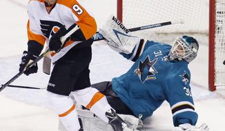 San Jose Sharks' Antti Niemi, front, falls back in front of Philadelphia Flyers' Steve Downie during the second period of an NHL hockey game, Monday, Feb. 3, 2014, in San Jose, Calif. (AP Photo/George Nikitin)