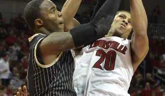 Louisville's Wayne Blackshear, right, battles Central Florida's Eugene McCrory for a rebound during the second half of an NCAA college basketball game on Saturday, Feb. 1, 2014, in Louisville, Ky. Louisville defeated UCF 87-70. (AP Photo/Timothy D. Easley)