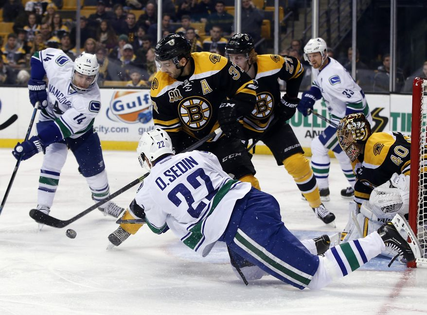 Vancouver Canucks left wing Daniel Sedin (22) passes the puck to teammate Alex Burrows (14) in front of Boston Bruins goalie Tuukka Rask (40), as Bruins' Patrice Bergeron (37) and Dougie Hamilton (27) defend during the first period of an NHL hockey game in Boston on Tuesday, Feb. 4, 2014. (AP Photo/Elise Amendola)