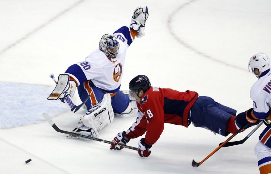 Washington Capitals right wing Alex Ovechkin (8), from Russia, falls as he tripped by New York Islanders defenseman Lubomir Visnovsky (11), from Slovakia, with goalie Evgeni Nabokov (20), from Russia, in the third period of an NHL hockey game, Tuesday, Feb. 4, 2014, in Washington. Visnovsky was penalized for tripping on the play. The Islanders won 1-0. (AP Photo/Alex Brandon)