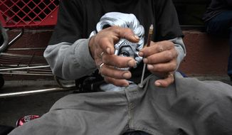 In this Monday, May 6, 2013 file photo, a drug addict prepares a needle to inject himself with heroin in front of a church in the Skid Row area of Los Angeles. (AP Photo/Jae C. Hong)