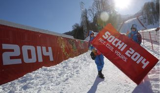 Volunteers put the finishing touches to the look of the finish area of the alpine skiing at the Sochi 2014 Winter Olympics, Wednesday, Feb. 5, 2014, in Krasnaya Polyana, Russia. (AP Photo/Christophe Ena)