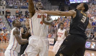 Florida center Patric Young (4) shoots as Missouri forward Johnathan Williams, III (3) defends during the second half of an NCAA college basketball game Tuesday, Feb. 4, 2014, in Gainesville, Fla. Florida won 68-58. (AP Photo/Phil Sandlin)