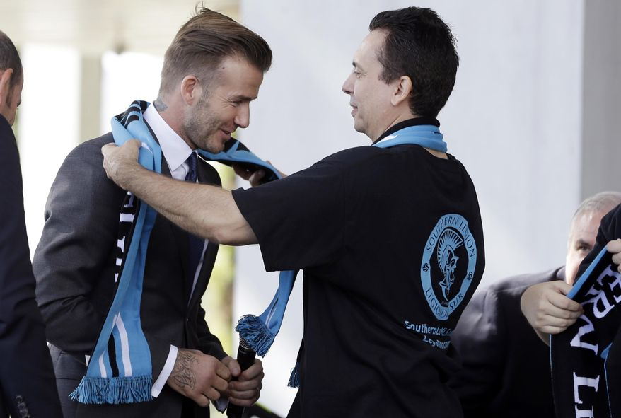 Former England soccer star David Beckham, left, is given a scarf by a fan from the Southern Legion soccer supporters group during a news conference where Beckham announced he will exercise his option to purchase a Major League Soccer expansion team in Miami, Wednesday, Feb. 5,  2014, in Miami. (AP Photo/Lynne Sladky)