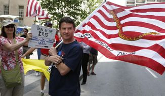 """FILE-In this May 21, 2013 file photo, Ted Stevenot, of Clermont County's Union Township carries a """"Don't Tread on Me"""" flag as Cincinnati area Tea Party groups protest the IRS scrutinization of tax-exempt status during a rally in downtown Cincinnati. Ohio's Republican and Democratic gubernatorial front-runners were headed Wednesday toward a primary-free showdown amid complaints both parties got too aggressive in pushing out challengers. The Republican primary field was cleared for first-term Gov. John Kasich earlier in January, when would-be challenger Ted Stevenot, a tea party favorite, left the race less than a week after joining it. (AP Photo/The Cincinnati Enquirer, Gary Landers, File)  MANDATORY CREDIT;  NO SALES"""