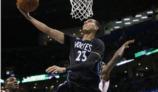 Minnesota Timberwolves guard Kevin Martin (23) shoots in front of Oklahoma City Thunder center Kendrick Perkins, left, and forward Serge Ibaka, right, during the first quarter of an NBA basketball game in Oklahoma City, Wednesday, Feb. 5, 2014. (AP Photo/Sue Ogrocki)