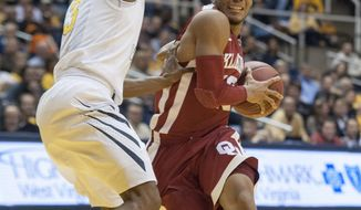 Oklahoma's Jordan Woodard, right, looks to drive by West Virginia's Juwan Staten during the first half of an NCAA college basketball game on Wednesday, Feb. 5, 2014, in Morgantown, W.Va. (AP Photo/Andrew Ferguson)