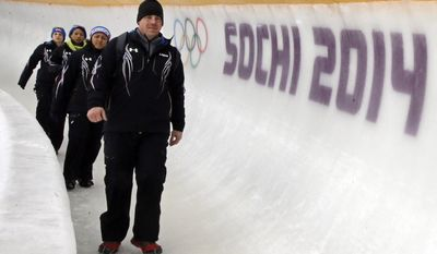 Todd Hays, right, coach of the United States women's team, walks the track with drivers Elena Meyers, left, Jazmine Fenlator, and Jamie Greubel, before a training run for the women's two-man bobsled at the 2014 Winter Olympics, Wednesday, Feb. 5, 2014, in Krasnaya Polyana, Russia. (AP Photo/Dita Alangkara)