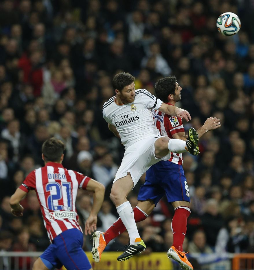 Real's Xabi Alonso, center, and Atletico's Raul Garca, right, jump for a high ball during a semifinal, 1st leg, Copa del Rey soccer derby match between Real Madrid and Atletico Madrid at the Santiago Bernabeu Stadium in Madrid, Wednesday Feb. 5, 2014. (AP Photo/Paul White)