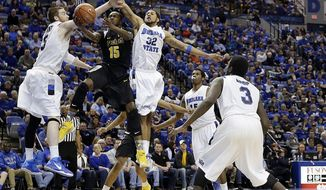 Wichita State guard Nick Wiggins (15) shoots between Indiana State defenders Justin Gant (5) and Khristian Smith (32) during the first half of an NCAA college basketball game in Terre Haute, Ind., Wednesday, Feb. 5, 2014. (AP Photo/AJ Mast)