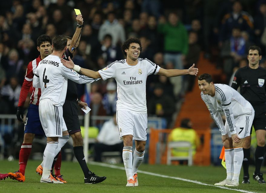 Real's Pepe, center, and Cristiano Ronaldo, right, laugh as Pepe gets a yellow card during the semifinal, 1st leg, Copa del Rey soccer derby match between Real Madrid and Atletico Madrid at the Santiago Bernabeu Stadium in Madrid, Wednesday Feb. 5, 2014. (AP Photo/Paul White)