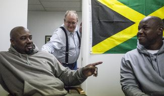 """In this photo taken on Jan. 24, 2014, Evanston attorney Paul Skog, center, jokes with Wayne Thomas and Wayne Blackwood at his law office in Evanston, Wyo. Skog, whose Main Street law office has doubled as the North American headquarters for the Jamaica Bobsled Federation since his efforts landed the team in Evanston for training in 1997, traveled to Sochi with the team as part of the Jamaican delegation. """"It fascinates me to think this has been an adventure for 17 years,"""" Skog says. (AP Photo/Casper Star-Tribune, Ryan Dorgan)"""
