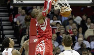 Houston Rockets center Dwight Howard, center, dunks over Phoenix Suns' Channing Fry, left, and Goran Dragic in the first half of an NBA basketball game on Wednesday, Feb. 5, 2014, in Houston. (AP Photo/Bob Levey)
