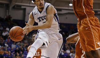TCU guard Kyan Anderson (5) passes the ball under the basket as Texas forward Jonathan Holmes (10) defends during the second half of an NCAA college basketball game Tuesday, Feb. 4, 2014, in Fort Worth, Texas. Texas defeated TCU 59-54. (AP Photo/Sharon Ellman)