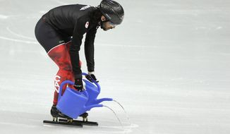 Canadian short track speed skating team member Charles Hamelin pours water on the ice during a training session at the Iceberg Skating Palace ahead of the 2014 Winter Olympics, Tuesday, Feb. 4, 2014, in Sochi, Russia. (AP Photo/Mark Baker)