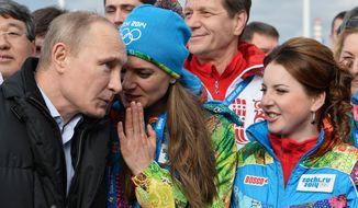 Russian President Vladimir Putin speaks with Olympic Village Mayor Elena Isinbaeva while visiting the Coastal Cluster Athletes Olympic Village ahead of the Sochi 2014 Winter Olympics on Wednesday, Feb. 5, 2014 in Sochi, Russia.  (AP Photo/Pascal Le Segretain, Pool)