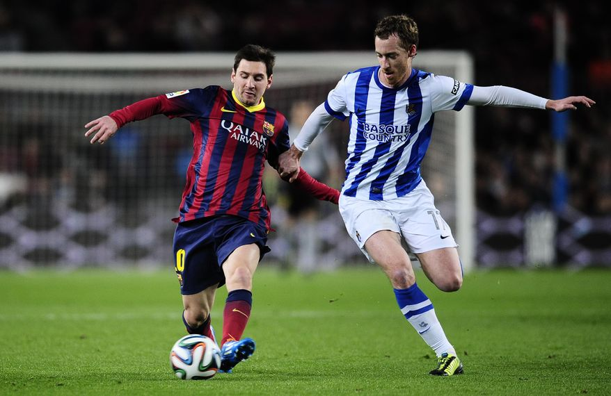 FC Barcelona's Lionel Messi, left, duels for the ball against Real Sociedad's Carlos Vela during a Copa del Rey soccer match at the Camp Nou stadium in Barcelona, Spain, Wednesday, Feb. 5, 2014. (AP Photo/Manu Fernandez)