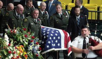 The casket of Utah County Sheriff's Sgt. Cory Wride arrives for funeral services at Utah Valley University Wednesday, Feb. 5, 2014, in Orem, Utah. Wride was killed on Jan. 30 on a rural highway about 35 miles south of Salt Lake City. Wride had stopped to check on a truck with its emergency lights on when he was shot twice while seated in his patrol car. (AP Photo/Rick Bowmer)