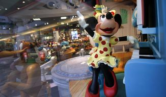 ** FILE ** In this Friday, Jan. 31, 2014, photo, a Minnie Mouse character plays piano in a Disney Store display window in Saugus, Mass. Walt Disney Co. reports quarterly financial results after the market closes on Wednesday, Feb. 5, 2014. (AP Photo/Elise Amendola)