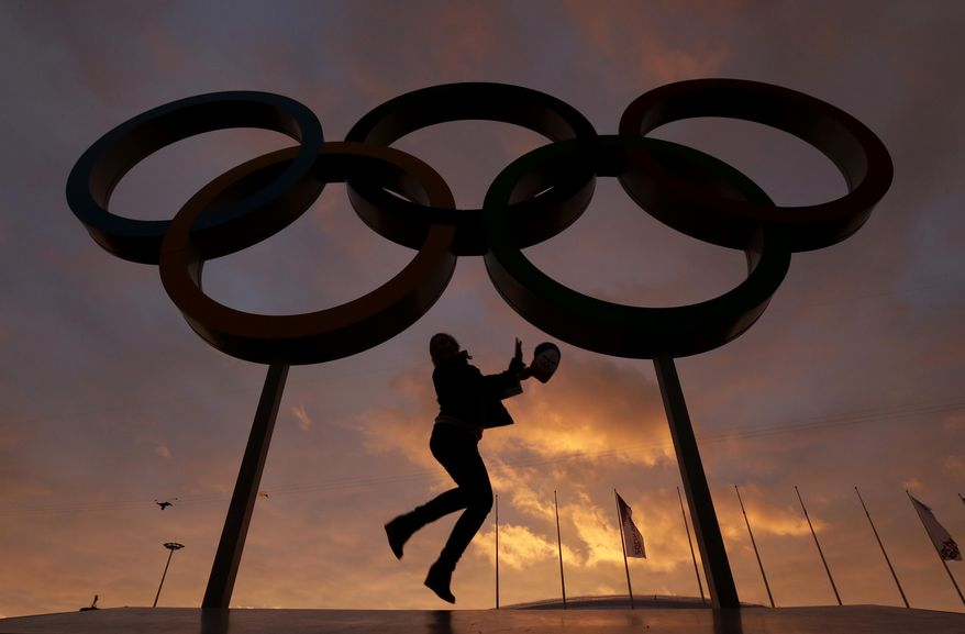 A woman poses for with the Olympic rings in Olympic Park as preparations continue for the 2014 Winter Olympics, Wednesday, Feb. 5, 2014, in Sochi, Russia. (AP Photo/Charlie Riedel)