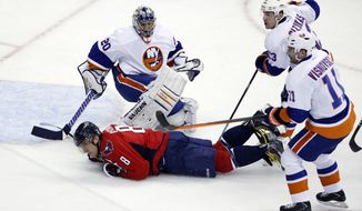 Washington Capitals right wing Alex Ovechkin (8), from Russia, slides by goalie Evgeni Nabokov (20), from Russia, after being tripped by defenseman Lubomir Visnovsky (11), from Slovakia, with center Casey Cizikas (53), in the third period of an NHL hockey game, Tuesday, Feb. 4, 2014, in Washington. Visnovsky was penalized for tripping on the play. The Islanders won 1-0. (AP Photo/Alex Brandon)