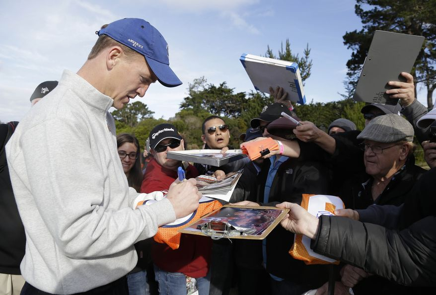 Denver Broncos quarterback Peyton Manning signs autographs on the fifth tee of the Pebble Beach Golf Links during a practice round at the AT&T Pebble Beach Pro-Am golf tournament Wednesday, Feb. 5, 2014, in Pebble Beach, Calif. (AP Photo/Eric Risberg)