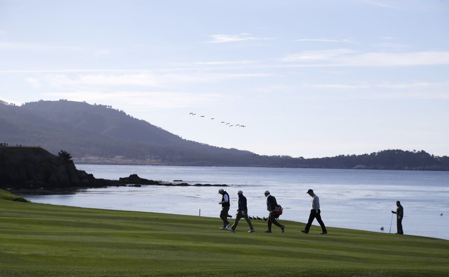 The playing group of Denver Broncos quarterback Peyton Manning, second from right, and New England Patriots head coach Bill Belichick, right, make their way up to the fourth green of the Pebble Beach Golf Links during a practice round of the AT&T Pebble Beach Pro-Am golf tournament Wednesday, Feb. 5, 2014, in Pebble Beach, Calif. (AP Photo/Eric Risberg)