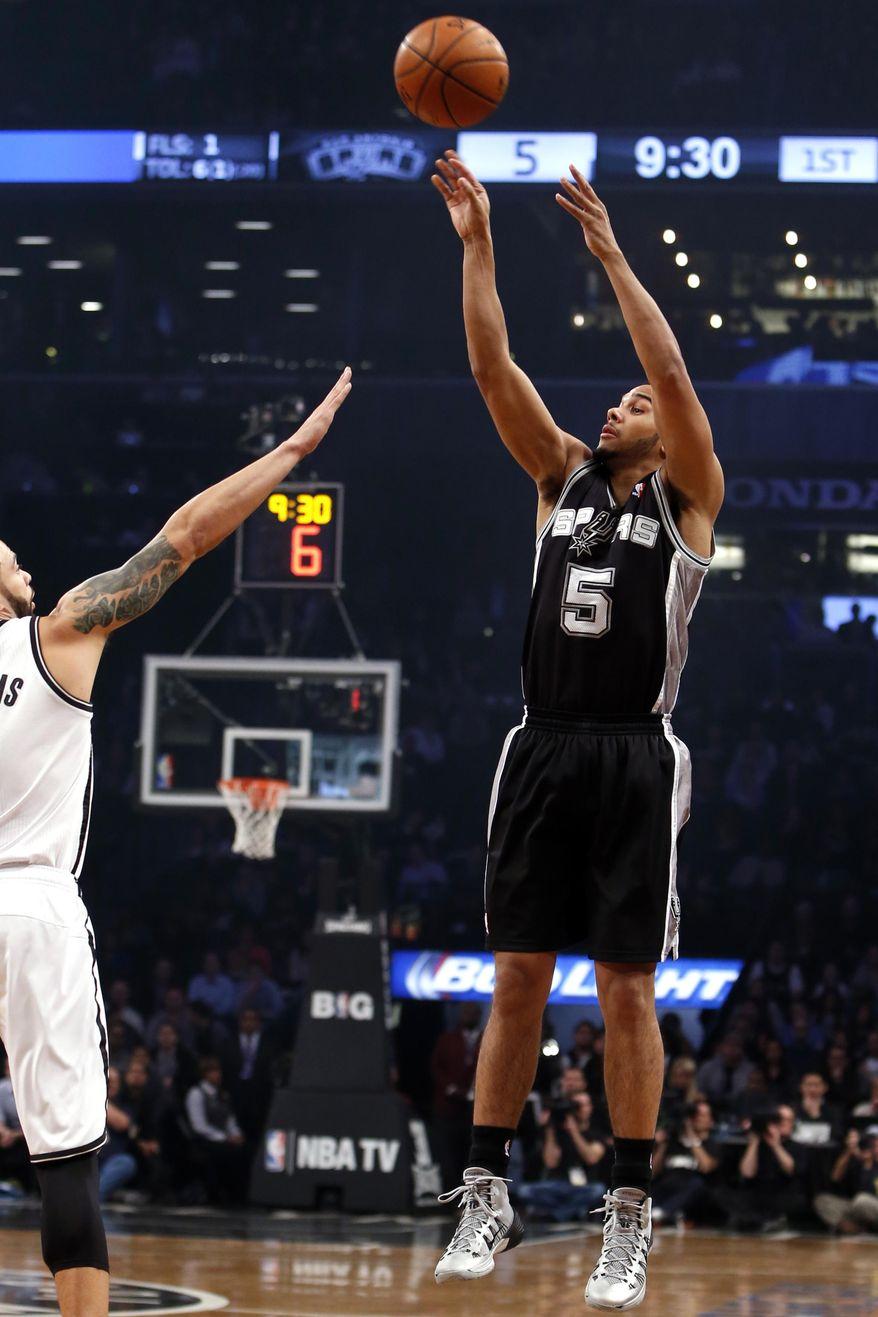 San Antonio Spurs' Cory Joseph (5) shoots against Brooklyn Nets' Deron Williams during the first half of an NBA basketball game on Thursday, Feb. 6, 2014, in New York. (AP Photo/Jason DeCrow)