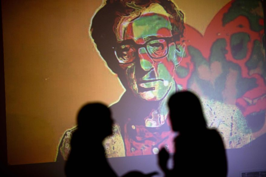 "An image of U.S. director Woody Allen is projected on a wall at an art exhibit titled ""Queremos tanto a Woody,"" or ""We so love Woody"" by Argentine artist Hugo Echarri in Buenos Aires, Argentina, Thursday, Feb. 6, 2014. The exhibit in honor of Allen was inaugurated just days after the artist faced renewed accusations that he molested Dylan Farrow, his then-7-year-old adopted daughter in 1992. (AP Photo/Rodrigo Abd)"