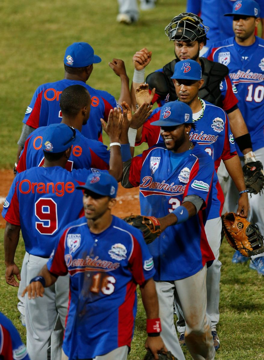 Players of the Dominican Republic celebrate after they defeated Cuba 9-2 during a Caribbean Series baseball game in Porlamar, Venezuela, Monday, Feb. 3, 2014. (AP Photo/Fernando Llano)