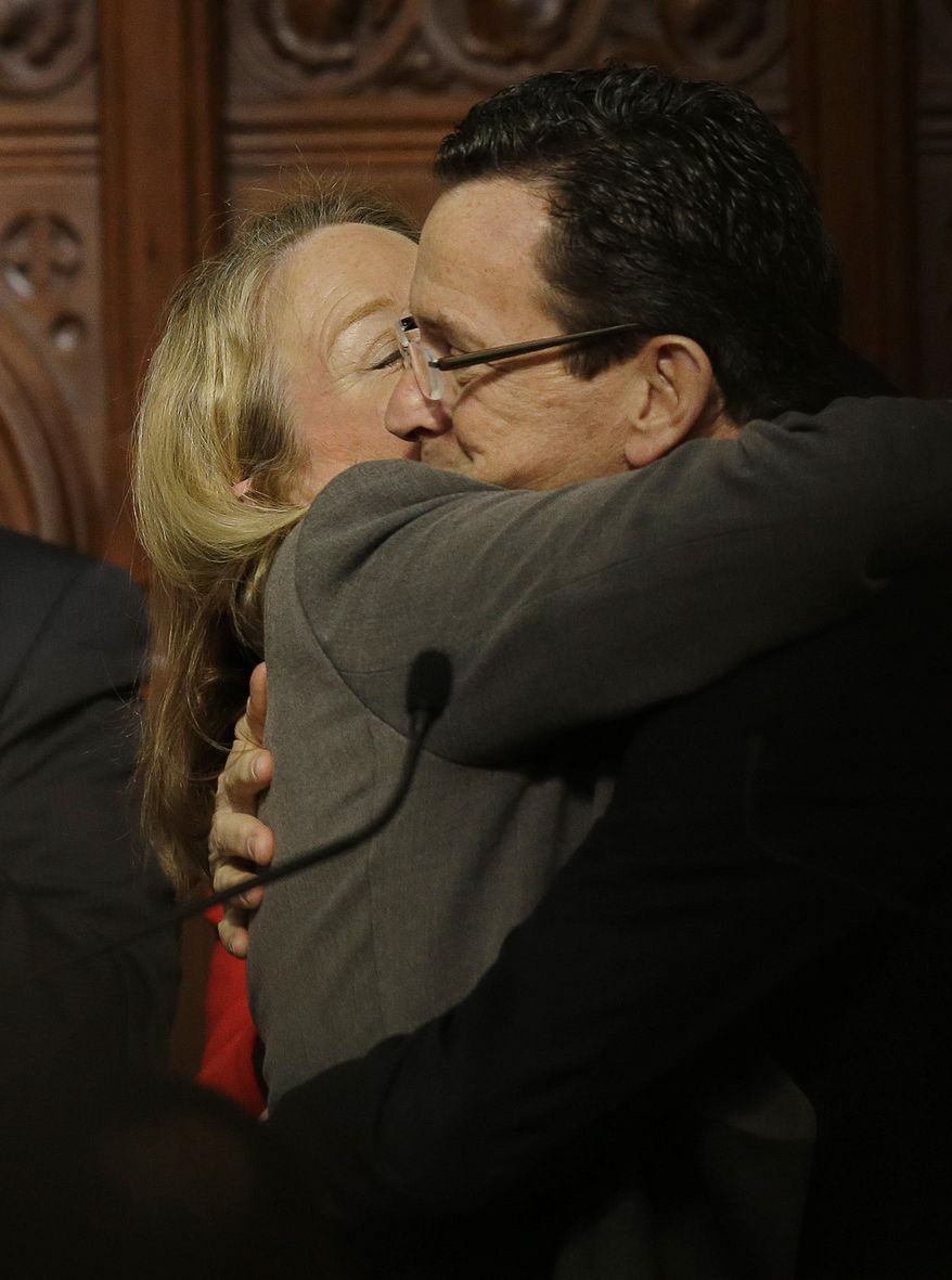 Connecticut Gov. Dannel P. Malloy receives a hug and a kiss from his wife Cathy after delivering his 2014 State of the State address in front of a joint session of the legislature in the House Chambers at the Capitol in Hartford, Conn., Thursday, Feb. 6, 2014. (AP Photo/Stephan Savoia)