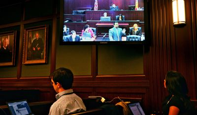 Members of the media monitor the jury selection progress while Cory Strolla, defense attorney for Michael Dunn, on screen second right, questions prospective jurors while State Attorney Angela Corey, on screen at second left, Wednesday, Feb. 5, 2014 in Jacksonville, Fla. (AP Photo/The Florida Times-Union, Bob Mack)
