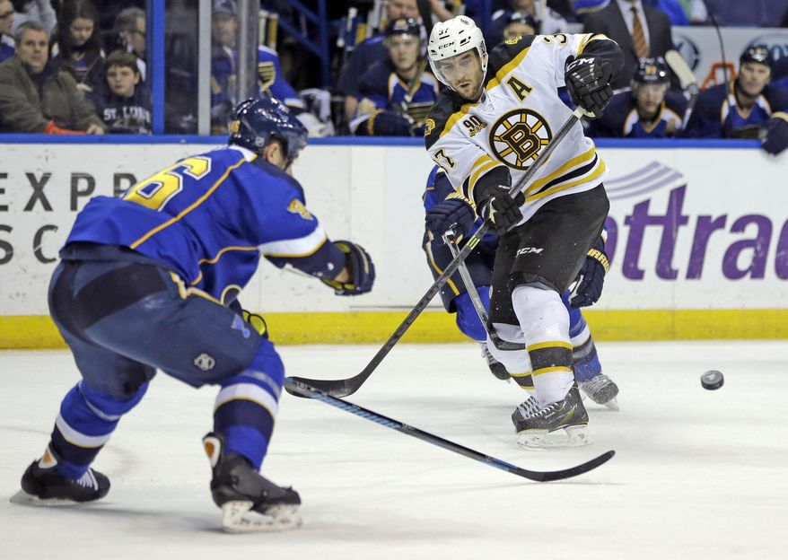 Boston Bruins' Patrice Bergeron, right, passes as St. Louis Blues' Roman Polak, of the Czech Republic, watches during the first period of an NHL hockey game Thursday, Feb. 6, 2014, in St. Louis. (AP Photo/Jeff Roberson)