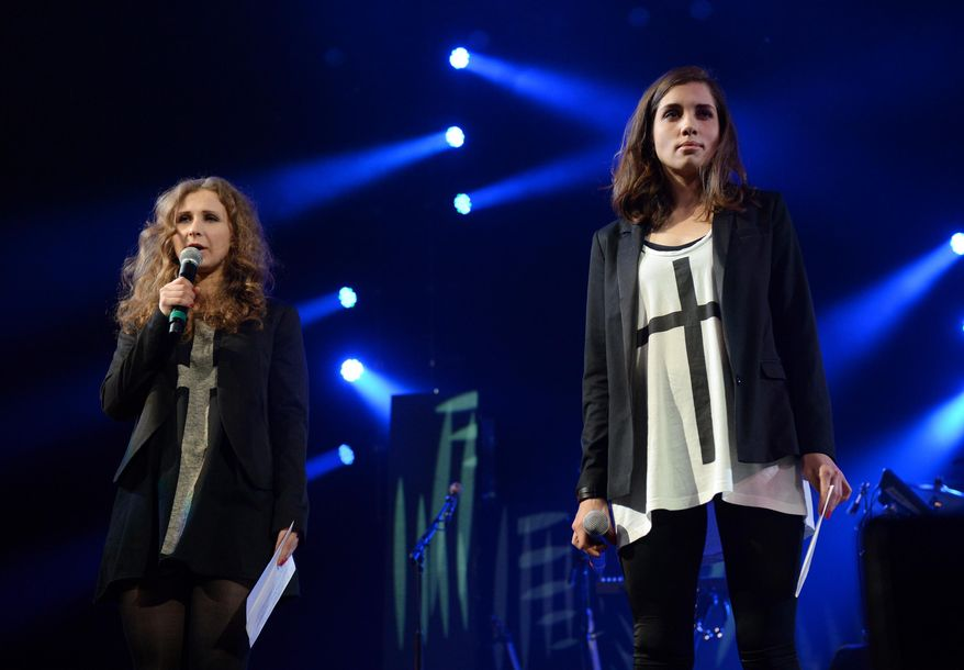 """Members of Pussy Riot, Maria Alekhina, left, and Nadya Tolokonnikova speak at Amnesty International's """"Bringing Human Rights Home"""" Concert at the Barclays Center on Wednesday, Feb. 5, 2014 in New York. (Photo by Evan Agostini/Invision/AP)"""