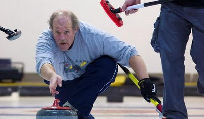 Preston Keres/Special to The Washington TimesGeorge Shirk of the Potomac Curling Club and Leticia Young of the Plainfield Curling Club compete in the regional championship held in Laurel, Md.