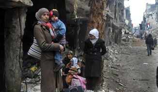 In this photo released by the Syrian official news agency SANA, residents of the besieged Yarmouk Palestinian refugee camp wait to leave the camp, on the southern edge of the Syrian capital Damascus, Syria, Tuesday, Feb. 4, 2014. Over the past six days the U.N. continued to distribute food parcels in the Palestinian camp where activists say at least 85 people have died as a result of lack of food and medicine since mid-2013. (AP Photo/SANA)