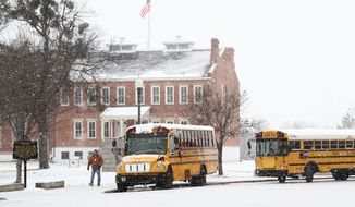 Public Schools buses wait to pick up students from a field trip to the Fort Smith Museum of History, Thursday, Feb. 6, 2014, as unexpected snowfall blanketed the area through the mid-morning and early afternoon hours. (AP Photo/The Southwest Times Record, Rachel Rodemann)