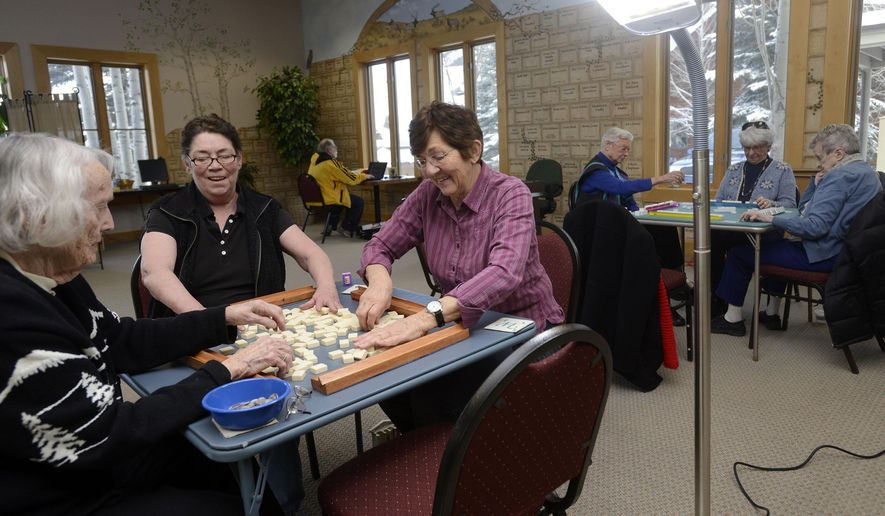From left, Barbara Daily, Karen Swaim and Sherry Kinsella play mahjong at the Jackson Hole Senior Center, basking in the glow of a 70-watt full spectrum floor lamp designed to combat the effects of SADS, or seasonal affective disorder.  The lights can be especially helpful for the elderly, who may have trouble getting outside into the sun during the winter. (Associated Press/Jackson Hole News & Guide, Price Chambers) **FILE**