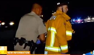 In this image taken from KFMB TV video, a California Highway Patrol officer handcuffs a firefighter after he refused an order to immediately move a fire engine that was blocking traffic at the scene of a car crash on Interstate 805 in San Diego County, Calif. on Tuesday, Feb. 4, 2014. The handcuffing was called an isolated incident by the agencies after the video of the confrontation spread on the Web and was broadcast nationwide. (AP Photo/KFMB TV)