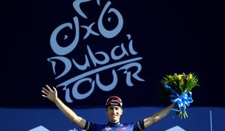 US cyclist Taylor Phinney, of BMC Racing Team, celebrates on the podium after he finished third and kept the leader's blue jersey after the Sport Stage of the 2nd day of Dubai Tour in Dubai, Thursday, Feb. 6, 2014. (AP Photo/Marwan Naamani, Pool)