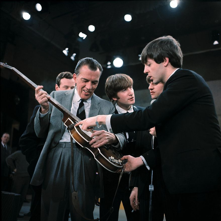 """FILE - In this Feb. 9, 1964 file photo, Paul McCartney, right, shows his guitar to host Ed Sullivan before the Beatles' live television appearance on """"The Ed Sullivan Show"""" in New York. The Beatles made their first appearance on """"The Ed Sullivan Show,"""" America's must-see weekly variety show, on Sunday, Feb. 9, 1964. And officially kicked off Beatlemania. (AP Photo, File)"""