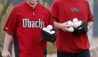Arizona Diamondbacks' Paul Goldschmidt, right, and Blake Lalli pick up baseballs after an informal workout with teammates a day prior to MLB spring training baseball starting for pitchers and catchers at the Diamondbacks training facility, Thursday, Feb. 6, 2014, in Scottsdale, Ariz. (AP Photo/Ross D. Franklin)