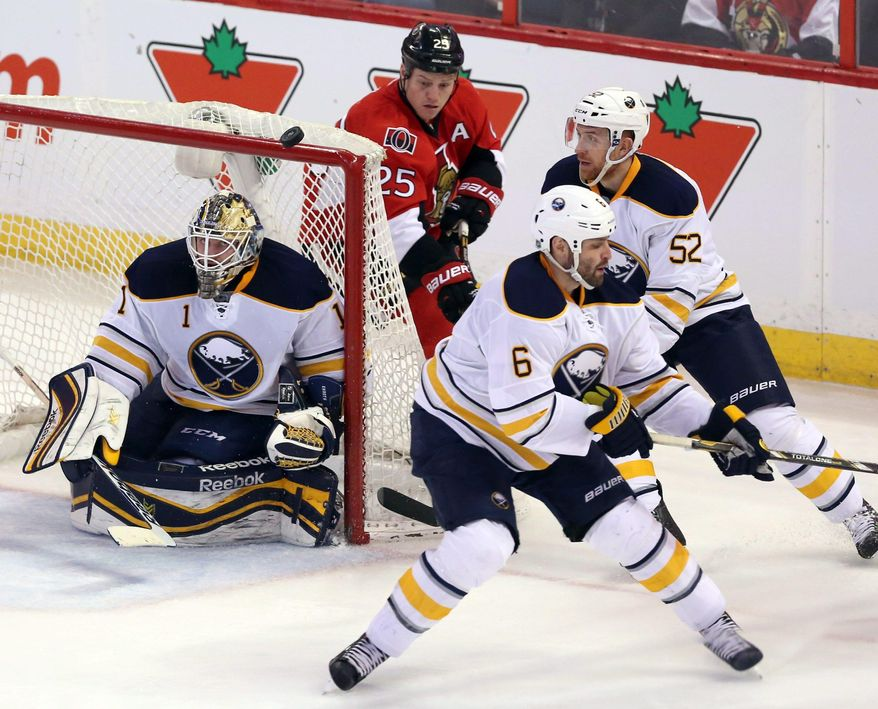 Ottawa Senators' Chris Neil (25), Buffalo Sabres goaltender Jhonas Enroth (1) and teammates Mike Weber (6) and Alexander Sulzer (52) all search for the puck during the second period of an NHL hockey game, Thursday, Feb. 6, 2014 in Ottawa, Ontario. (AP Photo/The Canadian Press, Fred Chartrand)