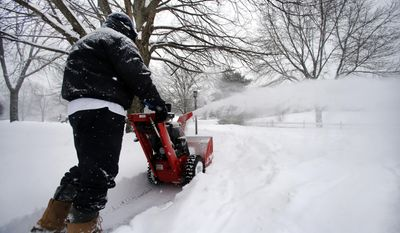 John McElroy clears snow from his property in North Andover, Mass., Wednesday, Feb. 5, 2014. A foot of snow or more is predicted to fall in parts of Massachusetts. (AP Photo/Elise Amendola)
