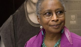 """FILE - In this April 23, 2009 file photo, Alice Walker stands in front of a picture of herself from 1974 as she tours her archives at Emory University, in Atlanta.  Walker, who turns 70 later this month, is thinking about her legacy. Over the past few years, the Pulitzer Prize-winning author has donated her papers to Emory University, permitted """"The Color Purple"""" to be released as an e-book and reached a deal with Simon & Schuster to publish excerpts from journals she has kept for decades. Walker also participated in the documentary """"Alice Walker: Beauty in Truth,"""" scheduled to air Friday, Feb. 7, 2014 on PBS stations as part of the """"American Masters"""" series. (AP Photo/John Amis)"""