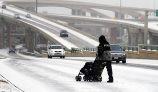A man pushes an empty stroller on a snow covered street in Dallas, Thursday, Feb. 6, 2014. A light snow made the morning commute difficult for a metropolitan area not accustomed to winter precipitation. (AP Photo/LM Otero)