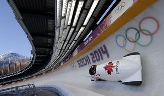 The CAN-1 sled from Canada takes a turn during a training run for the two-man bobsled at the 2014 Winter Olympics, Thursday, Feb. 6, 2014, in Krasnaya Polyana, Russia. (AP Photo/Michael Sohn)